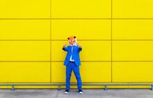 Man Wearing Vibrant Blue Suit And Tiger Mask Showing Two Middle Fingers In Front Of Yellow Wall