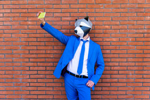Man Wearing Vibrant Blue Suit And Raccoon Mask Taking Smart Phone Selfie Against Brick Wall