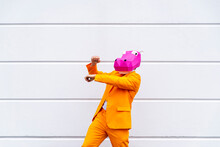 Man Wearing Vibrant Orange Suit And Hippo Mask Dancing In Front Of White Wall