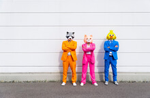 Three People Wearing Vibrant Suits And Animal Masks Posing Side By Side In Front Of White Wall