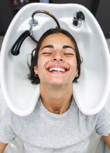 Smiling Woman Preparing To Wash Hair In Sink In Salon