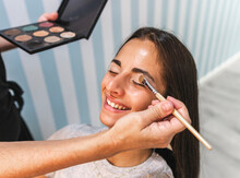 Crop Master Applying Makeup On Eyelid Of Client
