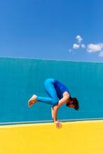Mid Adult Man Practicing Kakasana On Retaining Wall During Sunny Day