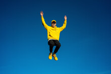 Carefree Boy With Arms Raised Jumping On Sunny Day