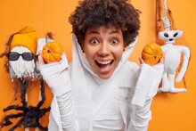 Surprised Cheerful Woman With Curly Hair Holds Two Small Pumpkins Exclaims Loudly Dressd Like Ghost Ready For Halloween Celebration Poses Around Creepy Toys. Glad Ghost Character Frightens You