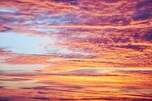 Bright Orange And Pink Sunset With Massive Sharp Cumulus Clouds. Majestic Nature Phenomenon And Dramatic Sky