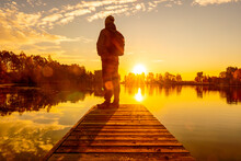 Man Standing On Pier Facing To The Sunset