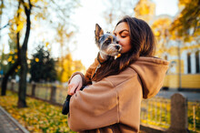 Bright Portrait Of A Joyful Dog-owner Female Hugging And Kissing Her York Terrier, Standing On The Street In Front Of The Yellow Building And Trees.