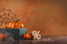 Pile Of Orange Halloween Pumpkins With Golden Spider Webs And Branches. Happy Halloween Party Decoration On Brown. Sale Or Discount With Percentage Sign. Copy Space