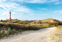Summer Evening View On Lighthouse And Sandy Landscape Around. Sandy Dirt Road For Bikers And Walkers In Foreground.