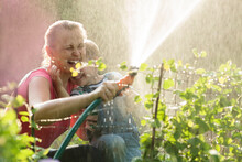 Laughing Mother And Son Playing With A Sprinkler