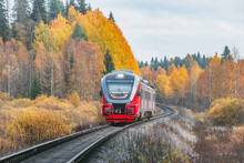 Passenger Train Moves At Autumn Day Time.