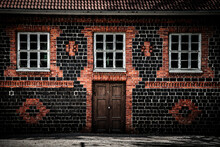 Wooden Entrance Door To A Brick Tiled House With Light Mortar And Three Old Damaged Glass Windows