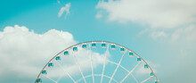 Ferris Wheel And White Cloud In Blue Pastel Sky