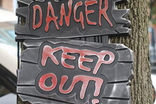 Danger Keep Out Sign Hanging On Tree Close Up