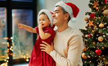 Winter Holidays And Family Concept - Happy Middle-aged Father And Baby Daughter In Santa Hat Looking Through Window Over Christmas Tree At Home