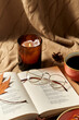 Leinwandbild Motiv autumn, season and leisure concept - open book of poems with glasses, cup of coffee and candle in holder burning on warm blanket at home