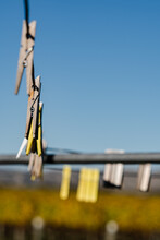 Vertical Shot Of Clothespins Hanging On A Rope Outdoors