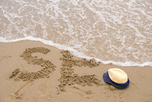 Sea Waves Washing Away The Letters On The Sand. Children's Sun Hat And Remnants Of The Word Sea.