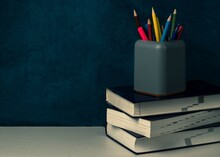 A Stack Of Books And A Gray Stationery Glass With Multi-colored Pencils On The Table. Back To School Concept