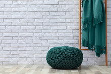 Stylish Knitted Pouf And Ladder With Plaid Near White Brick Wall Indoors, Space For Text. Interior Design