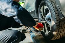 Car Service, The Car Is On A Lift, The Worker Removes / Installs The Wheel, He Has A Tool In His Hands