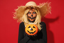 Young Scary Woman With Halloween Makeup Mask Wears Straw Hat Black Scarecrow Costume Hold Pumpkin Jack-o-lantern Isolated On Plain Red Background Studio Portrait. Celebration Holiday Party Concept