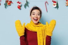 Amazed Astonished Vivid Young Woman 20s Wears Yellow Mittens Scarf Sweater Raised Hands Isolated On Plain Pastel Light Blue Background Studio Portrait. Happy New Year 2022 Celebration Holiday Concept.