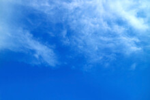 White Feathery Clouds Spread On Vibrant Blue Sky