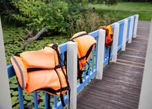 Three Orange Life Jackets On The Lakeside Bridge Fence. Fishing Water Safety Concept, Misadventure