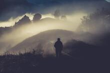 Man Walking In A Foggy Autumn Landscape