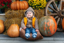 Happy Child With Pumpkins On Sunset. Smiling Baby Wearing Jeans And Yellow Jacket Posing In A Place Decorated With Pumpkins, Haystacks And Chrysanthemum Flowers. Autumn Activities For Children.