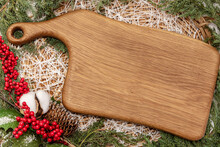 Wooden Cutting Board With Fir Tree Branches Rowan Red Berries Cotton And Pine Cone Lying In Wicker Basket As Christmas Holiday Concept