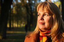 Close-up Portrait Of Middle Aged Caucasian Blonde Woman In Autumn Park. Bright Stylish Woman In Orange Coat And Shawl Of Neck Walking In October Park. Happy Fall Concept. Sunny Weather, Sunset