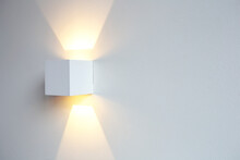 A Glowing Modern Aluminum Led Lamp On White Wall In Retro Home Decoration With Copy Space. Luxury Design
