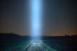 Smuga światła nad polną drogą, na tle nocnego, gwieździstego nieba.