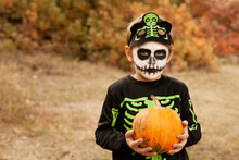Boy In Skeleton Costume With Face Painting In The Park With Pumpkin
