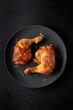 Leinwandbild Motiv Grilled chicken legs sprinkled with rosemary on a black plate.