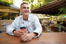 Young Man With Cup Of Coffee Sitting In Outdoor Cafe