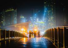Silhouettes Of People Walking On A Bridge At Night In Dubai, UAE