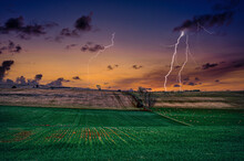 Shot Of Lightning Strikes Over A Grassy Field During Sunset