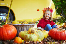 Adorable Toddler Girl In Maple Leaves Wreath Sitting On The Ground Near Many Pumpkins