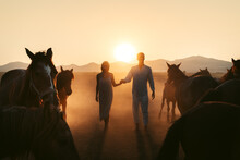Couple Walking On Field Together Near Horses At Sunset