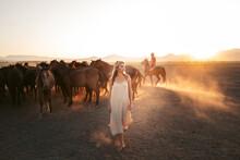 Woman With Horses In Field Under Sundown