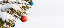 Christmas Panorama With Festive Decoration Baubles On Fir New Year Tree Capped With White Snow