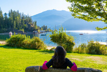 A Young Brunette Woman Seen From Behind As She Relaxes On A Park Bench At Kaslo Bay Park Along Kootenay Lake In Kaslo, BC, Canada.