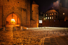 Cobblestone Street And Barbican Gate To The Old Town At Night, Warsaw, Poland