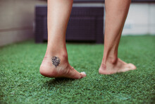 Close-up Of A Woman's Tattooed Foot Walking On Artificial Grass