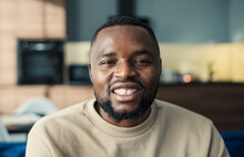 Head And Shoulders Portrait Of Handsome Young Black Man Looking At Camera And Smiling Happily Sitting On Sofa. Happy Guy With Beard Posing At Home