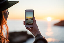 Young Woman Using Smartphone On Beach During Sunset, Ibiza